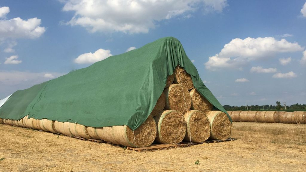 Toptex crop protection green sheet secured over the top of hay bales in a field.